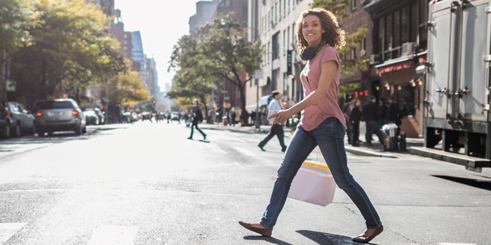 Happy woman in New York City holding shopping bags