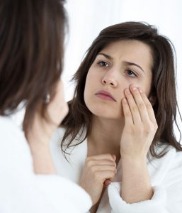Young woman looking in the mirror at her wrinkles